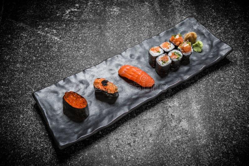Japanische Meeresfrüchtesushi, -rolle und -essstäbchen auf einem Schwarzblech stockbilder