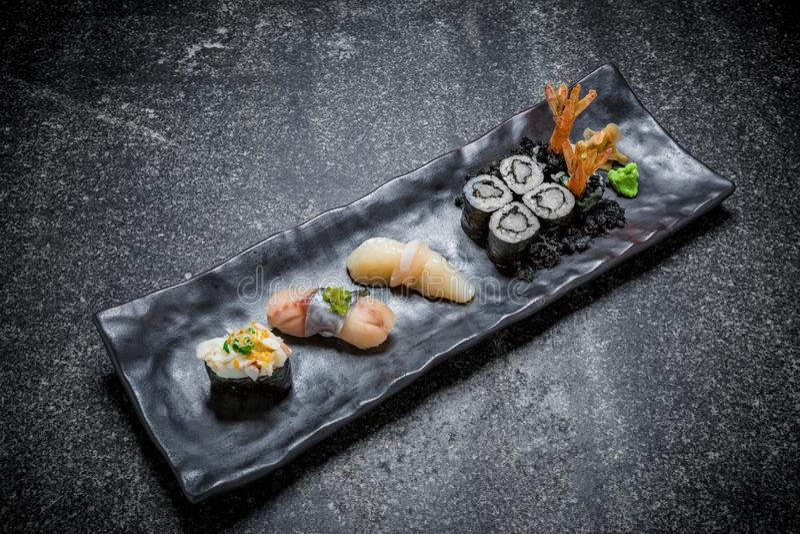 Japanische Meeresfrüchtesushi, -rolle und -essstäbchen auf einem Schwarzblech lizenzfreies stockfoto
