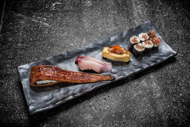 Japanische Meeresfrüchtesushi, -rolle und -essstäbchen auf einem Schwarzblech stockbild