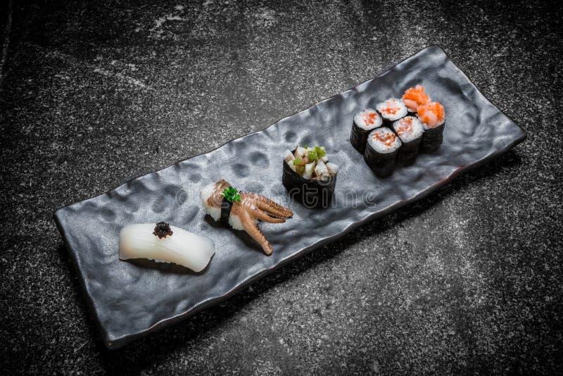 Japanische Meeresfrüchtesushi, -rolle und -essstäbchen auf einem Schwarzblech lizenzfreie stockfotos