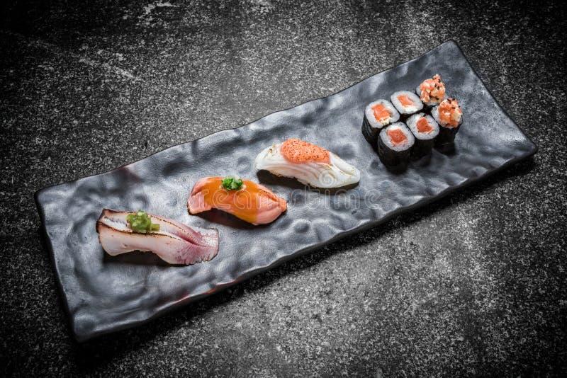 Japanische Meeresfrüchtesushi, -rolle und -essstäbchen auf einem Schwarzblech stockfotos