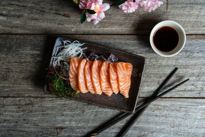 Japanische Nahrung des Lachssashimis mit Sojasoße auf Holztisch stockfoto
