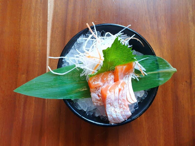 Japanische Nahrungsmittelart, Draufsicht des Lachsbauchsashimis mit Bambusblättern auf Eis lizenzfreie stockbilder