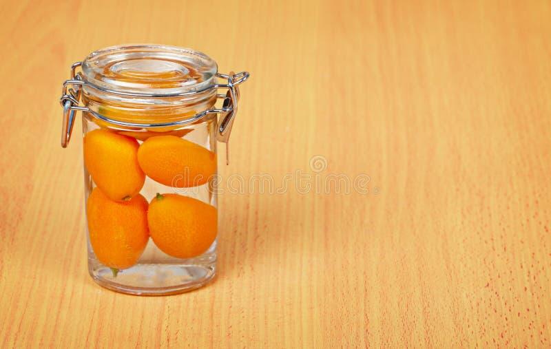 Japanische Orange innerhalb eines Glasglases auf hölzernem Hintergrund stockfotografie