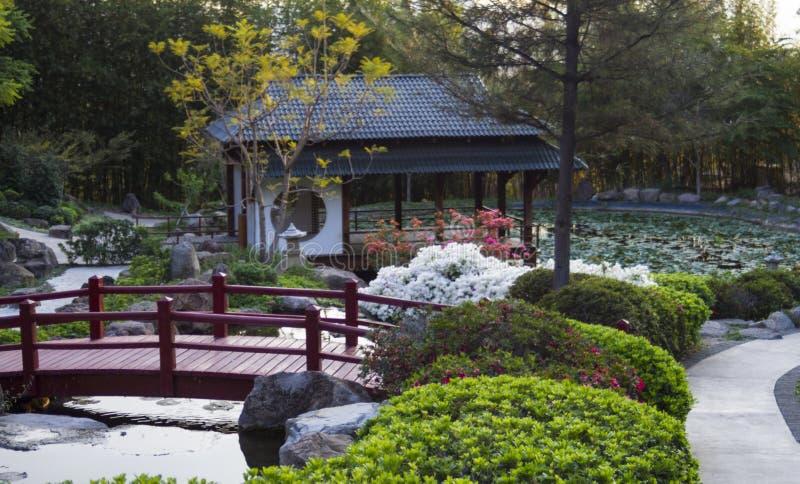 Japanische Pagode und rote Brücke im Zengarten stockfotografie