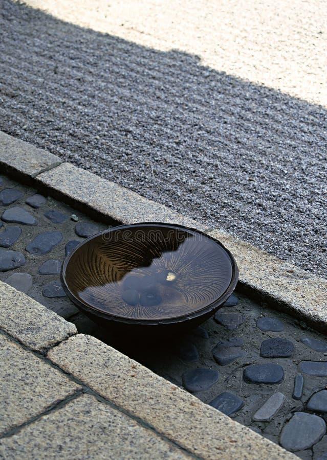 Japanische Schüssel gefüllt mit Wasser gehalten auf einem Steinbodenhintergrund lizenzfreies stockbild