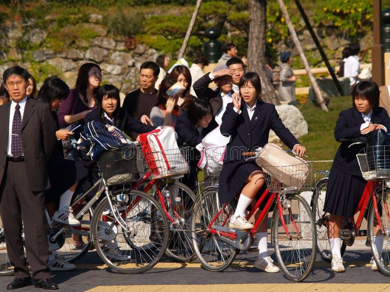 Japanische Schulmädchen, die zur Schule reiten stockbild
