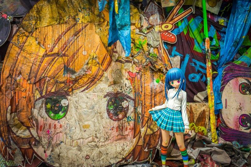 Japanische Schulmädchenskulptur vor Malerei von Takashi Murakami stockfotos