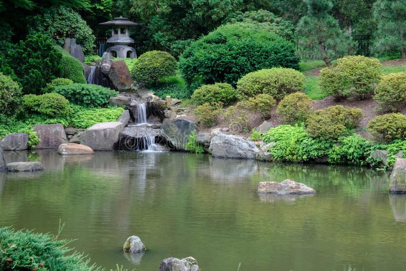 Japanische Steinlaternen und Wasserfall in Koi Fish Pond an lizenzfreie stockfotografie
