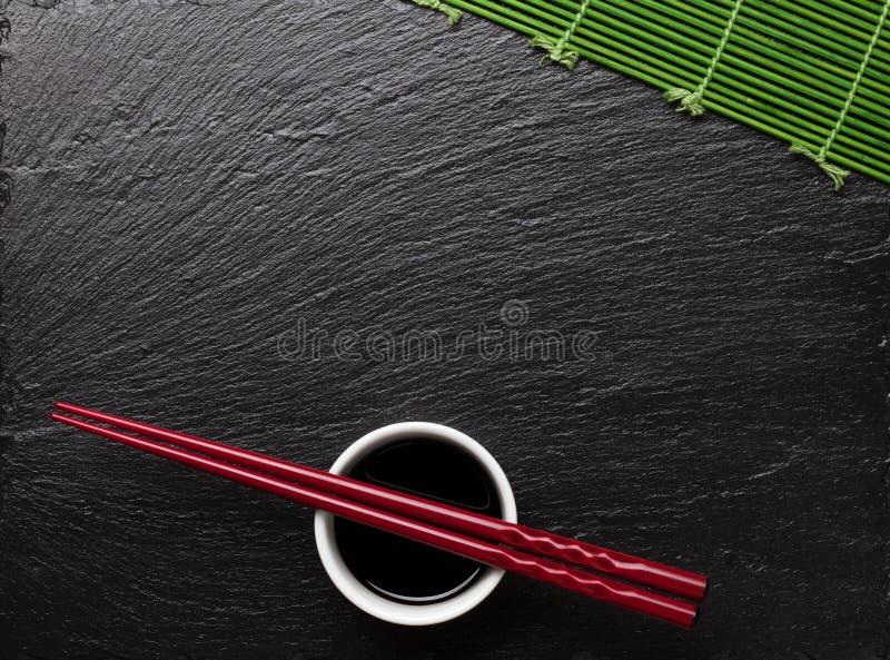 Japanische Sushiessstäbchen über Sojasoßenschüssel lizenzfreie stockfotos