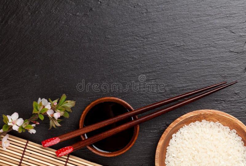 Japanische Sushiessstäbchen, Sojasoßenschüssel, Reis und Kirschblüte-bloss lizenzfreies stockbild