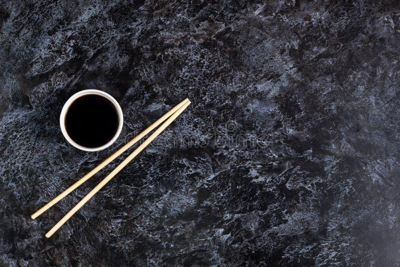 Japanische Sushiessstäbchen und Sojasoße auf schwarzem Hintergrund Draufsicht mit Copyspace stockfotos
