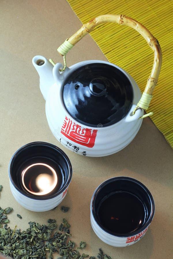 Japanische Teezeremonie, weißer Porzellanteetopf mit Bambusgriff und Hieroglyphen mit zwei Teeschalen, grüner Tee zerstreuten und lizenzfreies stockbild