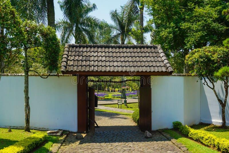 Japanische Torart mit weißer Wand und traditioneller Form mit Felsen oder Steinbahn - Foto lizenzfreie stockfotos