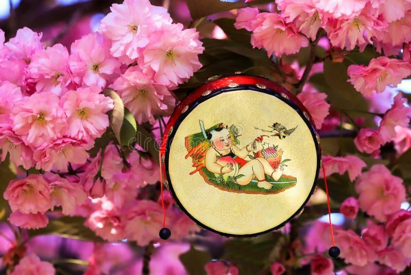 Japanische Trommel mit einem lustigen Muster auf dem Hintergrund eines bl?henden Kirschbl?te-Baums, Kirsche stockbild