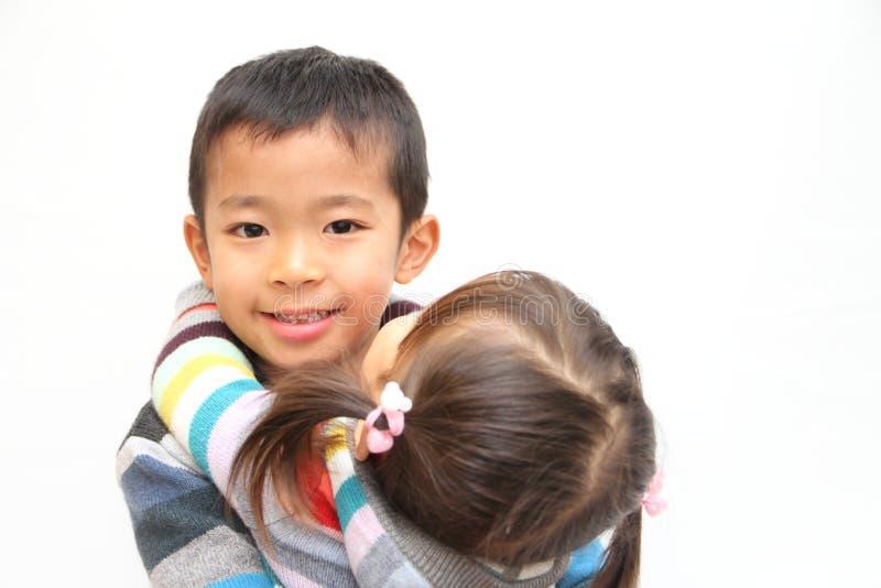 Japanischer Bruder und Schwester, die sich umarmt stockbilder
