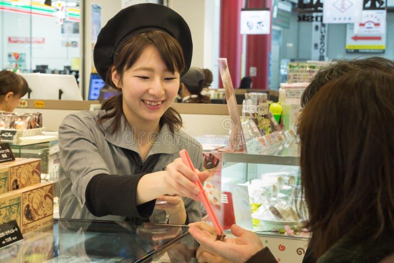 Japanischer Frauenbäcker bietet Produkte an, um zu schmecken lizenzfreies stockbild