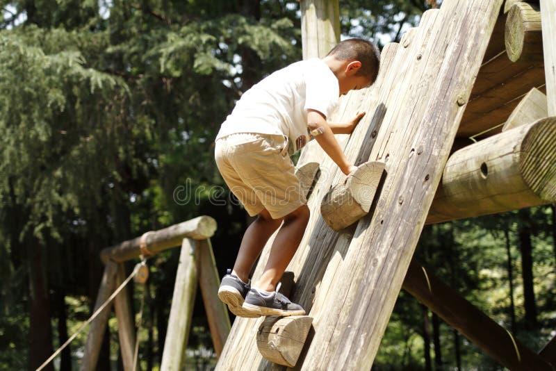 Japanischer Junge, der auf der Wand klettert stockfotografie