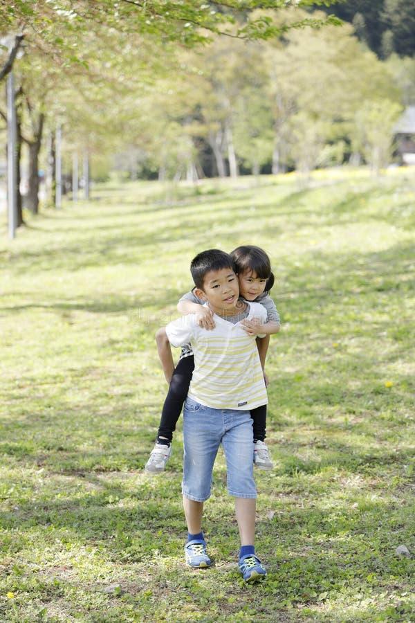 Japanischer Junge, der seine Schwester in seinem zurückbringt stockbild