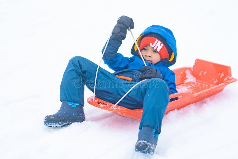 Japanischer Junge schiebt hinunter den Schneeschlitten in Gala Yuzawa Ski-Erholungsort lizenzfreie stockfotos