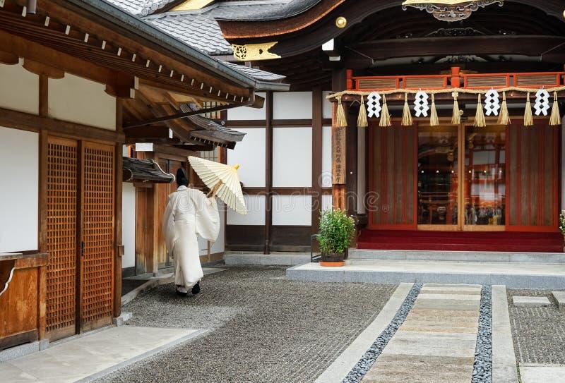 Japanischer Mönch im weißen Kleid von hinten an draußen im Tempel Kyoto lizenzfreies stockfoto