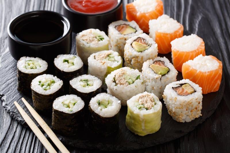 Japanisches Lebensmittel: ein Menü von Rollen mit Meeresfrüchtenahaufnahme mit Soßen stockfoto