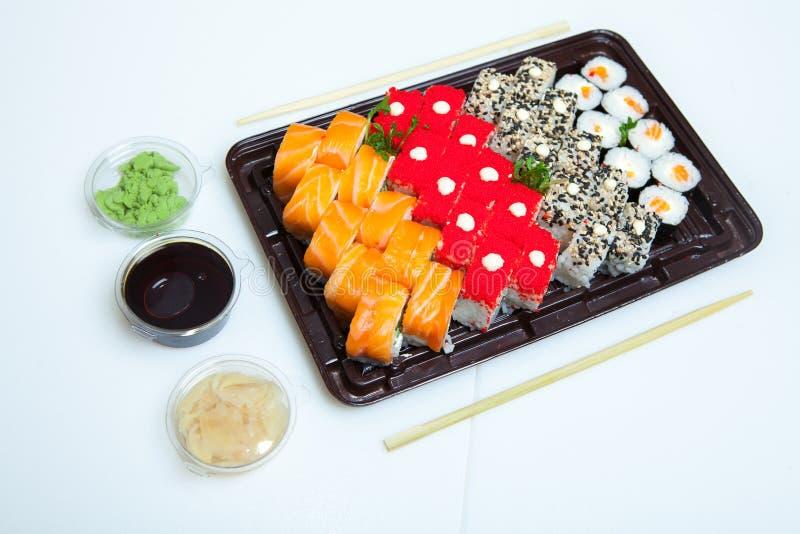 Japanisches Lebensmittel rollt im Plastikkasten Sushisatz in einem Plastikpaketabschluß oben lokalisiert auf einem weißen Hinterg stockbild
