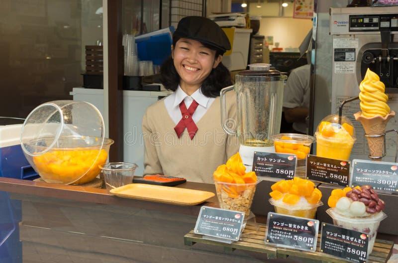 Japanisches Mädchen, das Mangoeiscreme verkauft stockbild