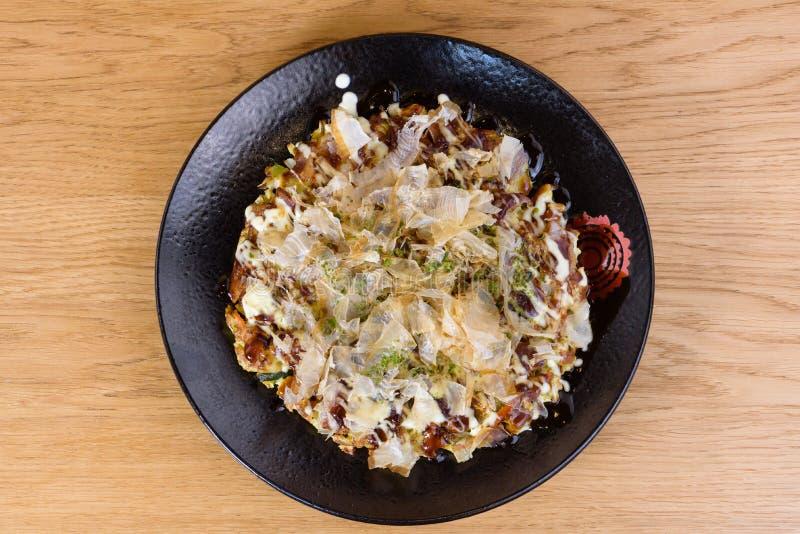 Japanisches Omelett Okonomiyaki, mit Eiern, Wirsingkohl, Mayonnaise, Karotte, Zucchini, Ingwer, getrockneter Meerespflanze und Ka lizenzfreies stockbild