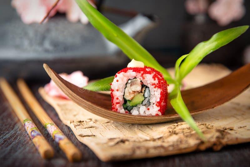JapanKalifornien rulle med ålen, avokadot, gurkan, kräm med Philadelphia ost, tobikokaviaren och japanmajonnässushi fotografering för bildbyråer