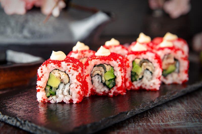 JapanKalifornien rulle med ålen, avokadot, gurkan, kräm med Philadelphia ost, tobikokaviaren och japanmajonnässushi arkivfoto