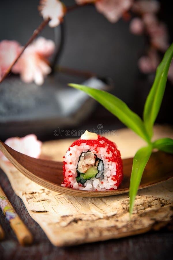 JapanKalifornien rulle med ålen, avokadot, gurkan, kräm med Philadelphia ost, tobikokaviaren och japanmajonnässushi royaltyfri foto