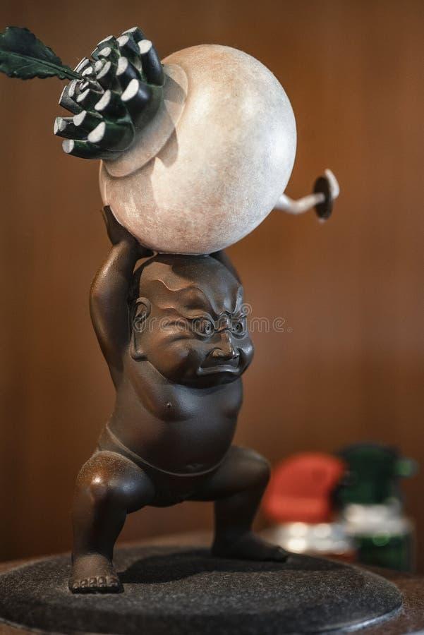 Japans ceramisch beeldjesymbool Japans ceramisch beeldje van een mens met een radijs De beeldjeherinnering Achtergrond stock fotografie