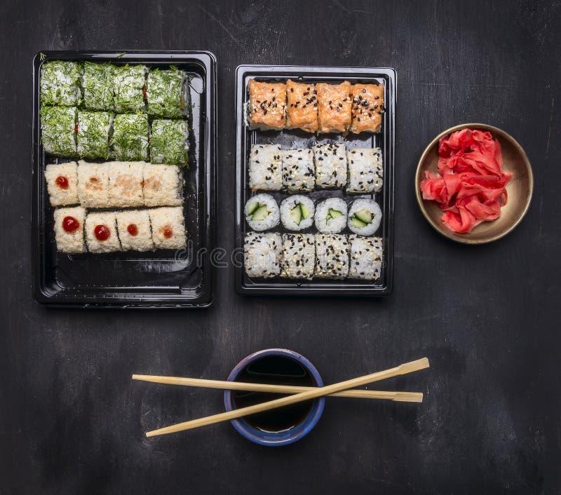 Japans snel die voedsel, sushi met diverse ingrediënten in plastic containers op donkere rustieke achtergrond, hoogste mening wor stock fotografie