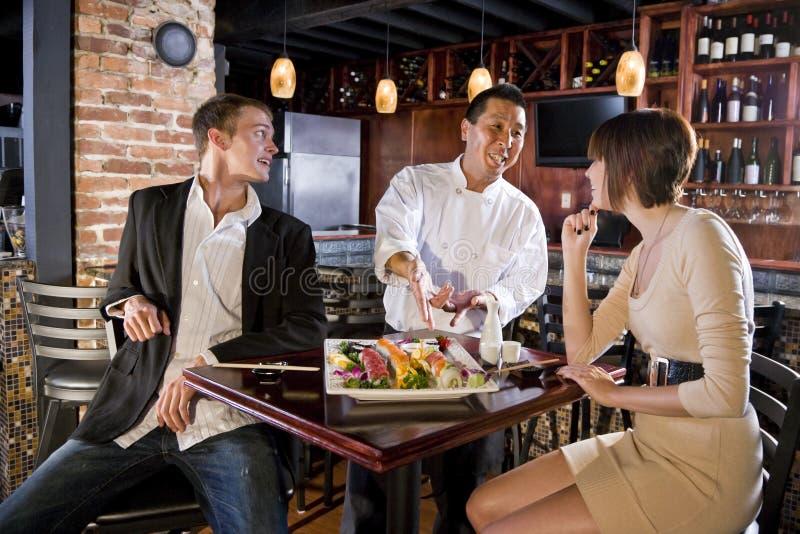 Japans sushirestaurant, chef-kok dienende klanten stock afbeeldingen
