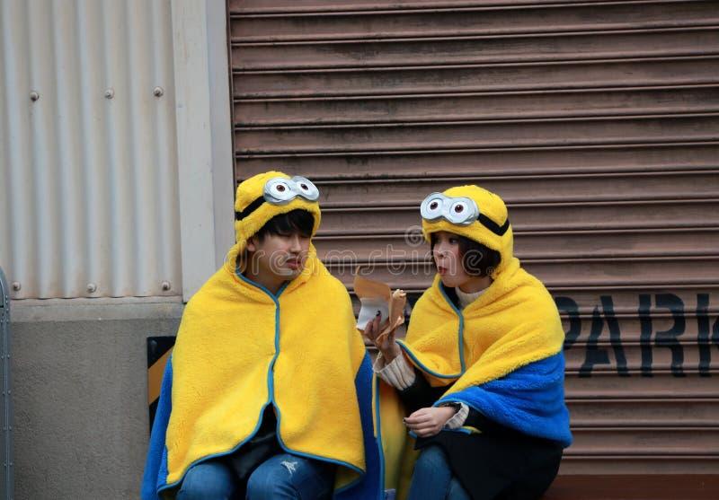Japanse adolescent van meisje en jongen in kap en deken van minion bij Universele Studio's Japan stock afbeelding