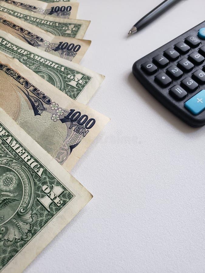 Japanse bankbiljetten, Amerikaanse dollarrekeningen, calculator en zwarte pen royalty-vrije stock afbeelding
