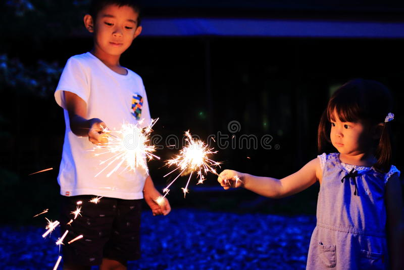 Japanse broer en zuster die handbediend vuurwerk doen stock afbeeldingen