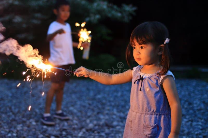 Japanse broer en zuster die handbediend vuurwerk doen stock afbeelding