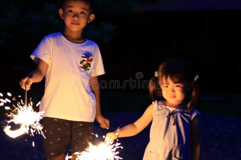 Japanse broer en zuster die handbediend vuurwerk doen royalty-vrije stock foto's