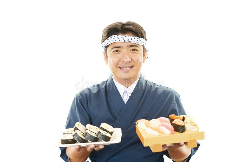 Japanse chef-kok met een plaat van sushi stock foto's