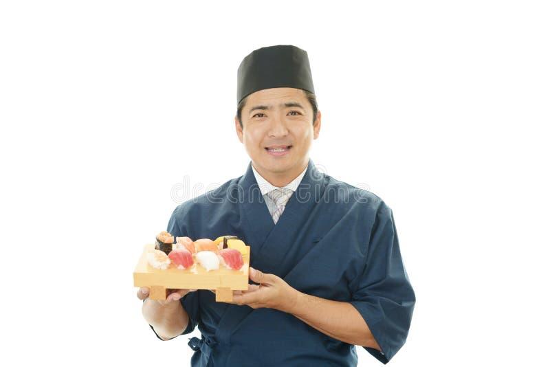 Japanse chef-kok met een plaat van sushi royalty-vrije stock afbeelding