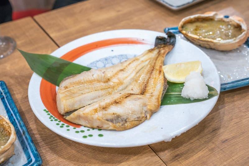 Japanse gekookte vissen in schotel op houten lijst bij Japans restaurant 24 open uren stock foto's
