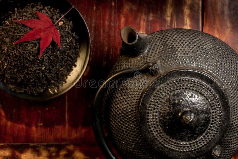 Japanse ijzertheepot en hoop van theebladen vanaf bovenkant. stock fotografie