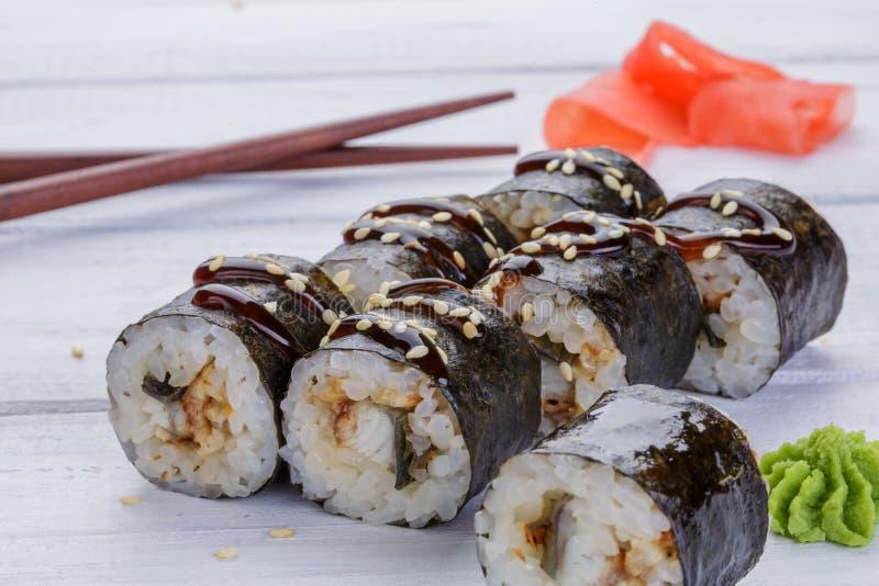Japanse Keuken - Sushi en Broodjes met Zeevruchten, Groenten, Roomkaas op een witte houten achtergrond Broodjes, gember, wasabi stock foto's