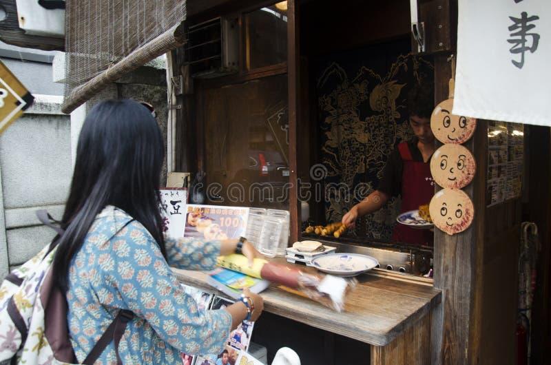 Japanse mensen die Japanse de snackstijl koken van Mitarashi Dango bij royalty-vrije stock fotografie