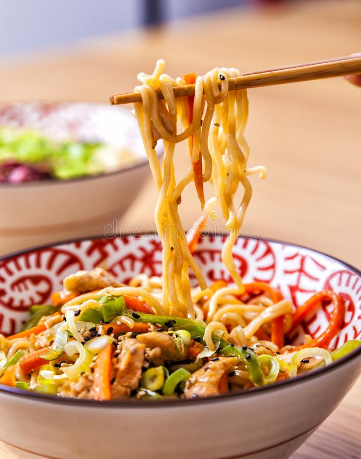 Japanse noedels in een kom met groenten stock afbeelding