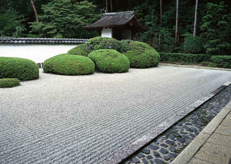 Japanse openluchttuinweg met de groene struiken en achtergrond van de steenbevloering stock fotografie