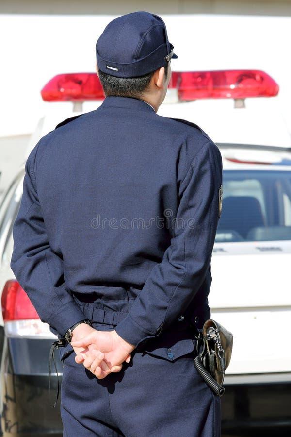 Japanse politieman met patrouillewagen stock afbeeldingen