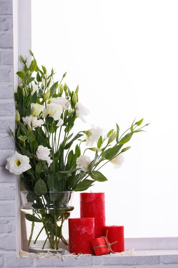Japanse rozen in een vaas van water naast kaarsen en een kleine gift op de vensterbank royalty-vrije stock afbeelding